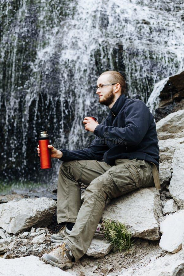 Um indivíduo novo bebe o chá ou o café de uma garrafa térmica, sentando-se nas pedras perto de uma cachoeira imagens de stock