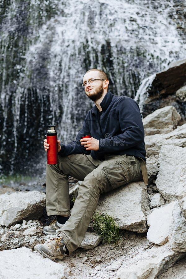 Um indivíduo novo bebe o chá ou o café de uma garrafa térmica, sentando-se nas pedras perto de uma cachoeira imagem de stock