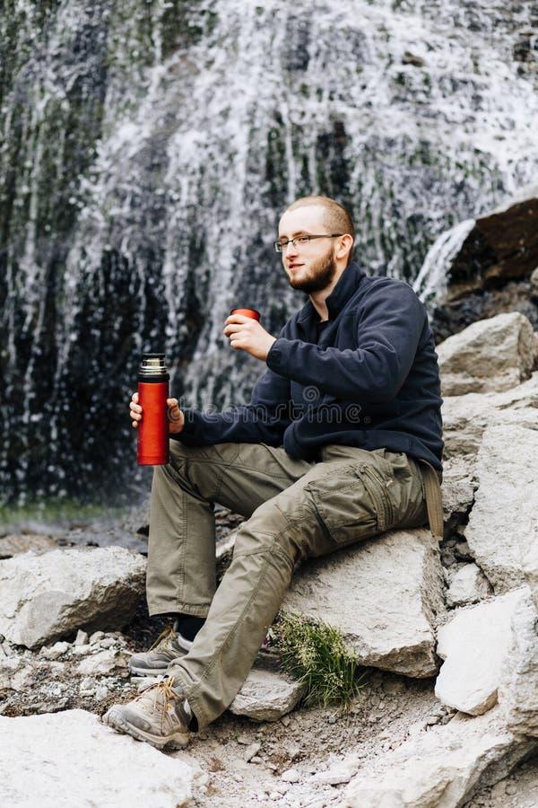 Um indivíduo novo bebe o chá ou o café de uma garrafa térmica, sentando-se nas pedras perto de uma cachoeira imagens de stock royalty free