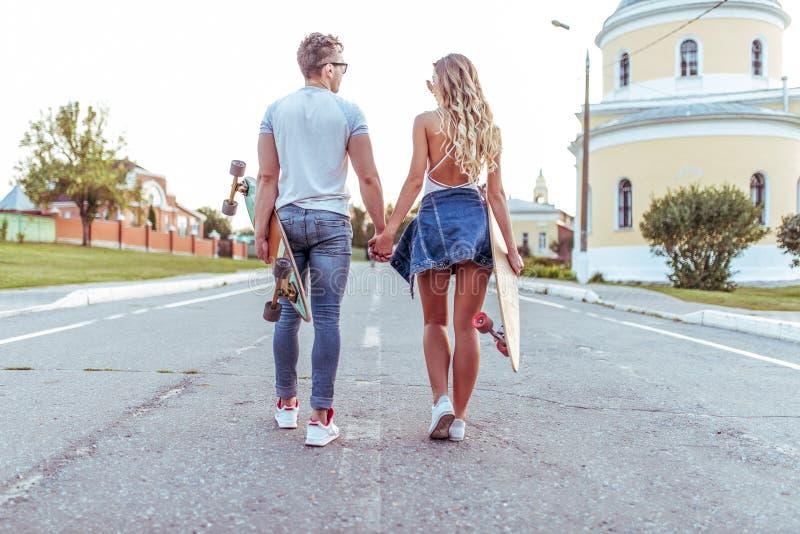 Um indivíduo novo da menina dos pares está andando a cidade do verão, vista da parte traseira Nas mãos dos skates, longboard Adol foto de stock royalty free