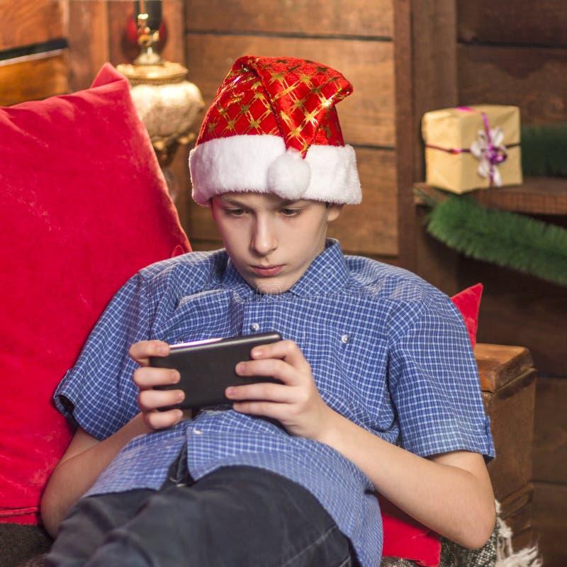 Um indivíduo novo em um chapéu de Santa Claus, em uma camisa quadriculado azul, senta-se no canto do ` s do ano novo, guarda-se s fotografia de stock royalty free