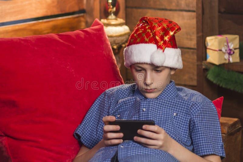 Um indivíduo novo em um chapéu de Santa Claus, em uma camisa quadriculado azul, senta-se no canto do ` s do ano novo, guarda seu  imagem de stock royalty free