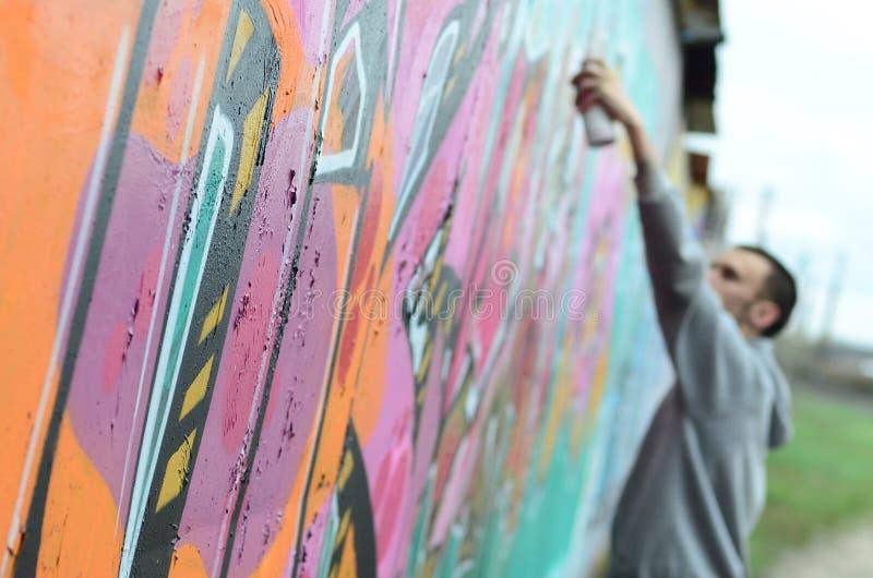 Um indivíduo novo em um hoodie do cinza pinta grafittis em c cor-de-rosa e verde fotografia de stock