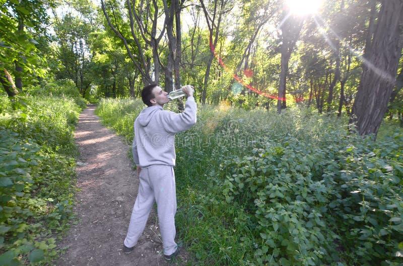 Um indivíduo novo em um terno cinzento dos esportes bebe a água de uma garrafa amo imagens de stock royalty free