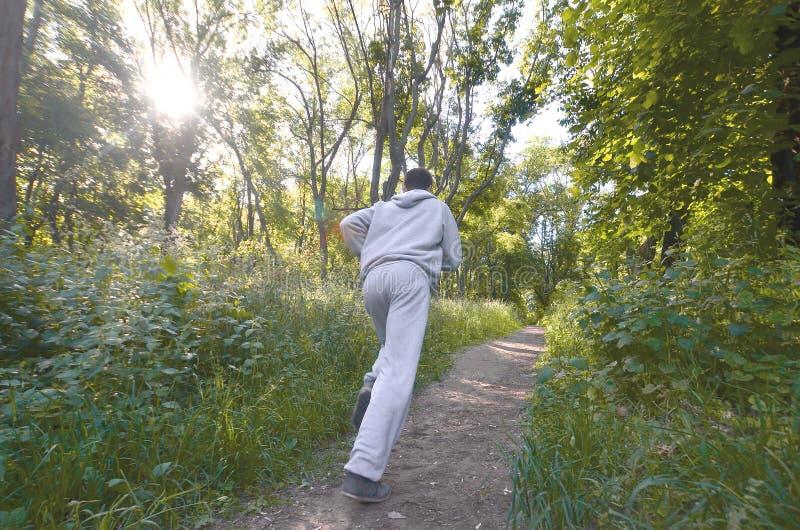 Um indivíduo novo em um terno cinzento dos esportes corre ao longo do trajeto entre foto de stock