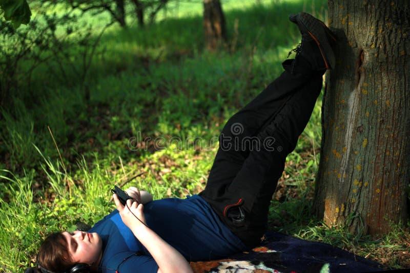 Um indivíduo novo na roupa escura está encontrando-se na grama com seus pés levantados e está olhando-se seu telefone celular O h foto de stock