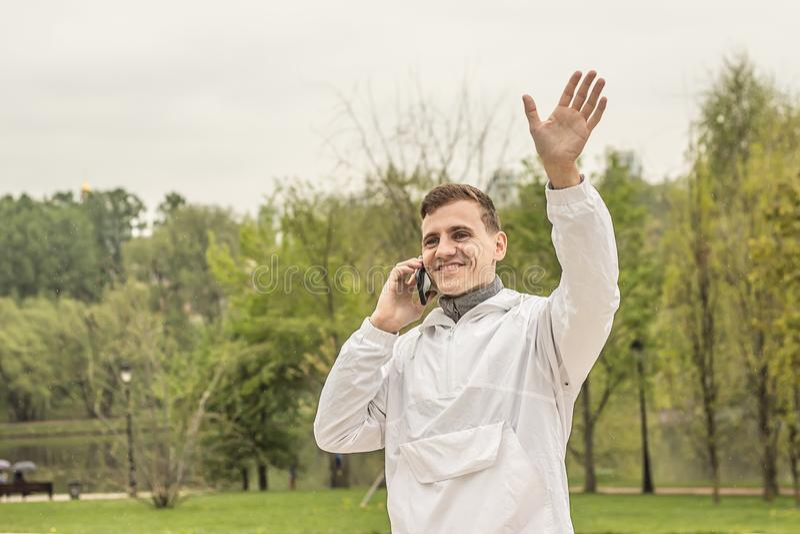 Um indivíduo novo que acena sua mão e que fala no telefone fotografia de stock royalty free