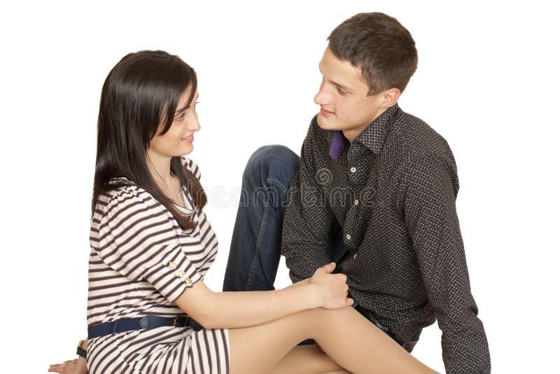 Um indivíduo novo que senta-se ao lado de uma menina foto de stock royalty free