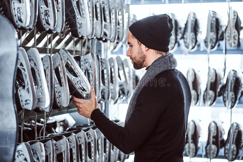 Um indivíduo novo que veste a roupa morna que escolhe um par de patins em um interior do aluguer do patim foto de stock