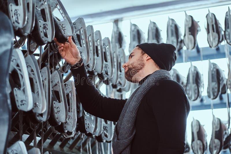 Um indivíduo novo que veste a roupa morna que escolhe um par de patins em um interior do aluguer do patim imagem de stock