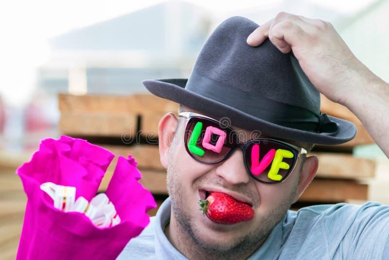Um indivíduo novo, romântico, sorrindo em vidros escuros com as morangos do amor e da baga da inscrição em sua boca dá um ramalhe imagens de stock