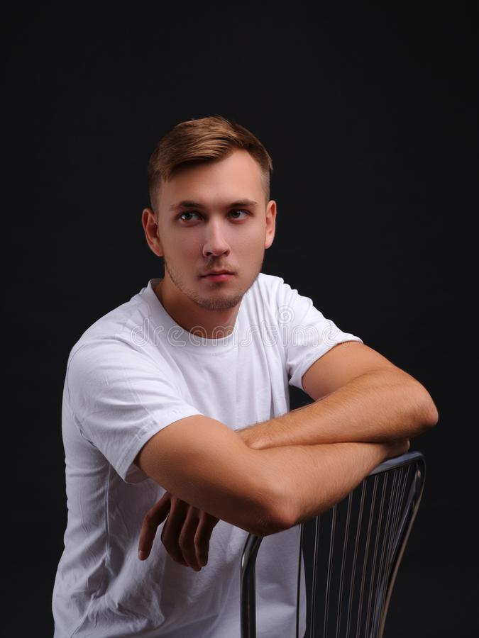 Um indivíduo novo, sentando-se em uma cadeira e olhando na distância Em um fundo preto imagens de stock