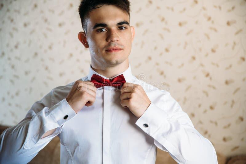 Um indivíduo novo veste uma borboleta vermelha Retrato de um indivíduo de cabelo escuro bonito com sardas em uma camisa branca Um imagens de stock royalty free