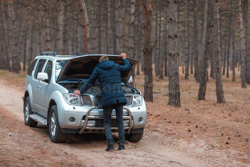 Um indivíduo vestiu-se em um revestimento morno, pares na capa de um carro quebrado, na floresta do outono imagens de stock