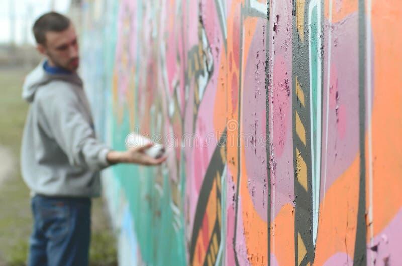 Um indiv?duo novo em um hoodie do cinza pinta grafittis em c cor-de-rosa e verde fotos de stock