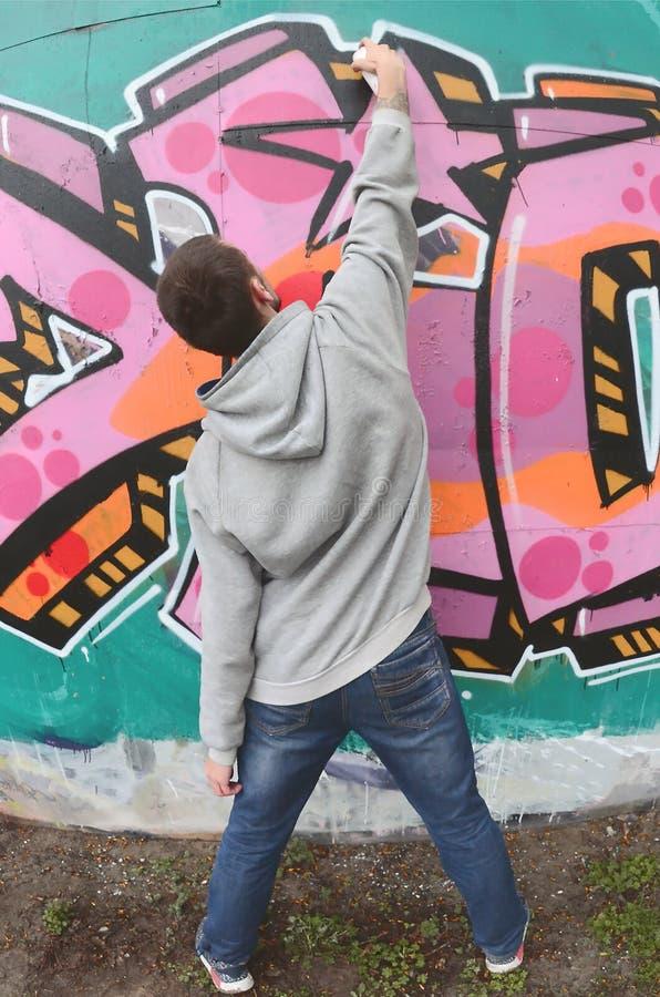 Um indiv?duo novo em um hoodie do cinza pinta grafittis em c cor-de-rosa e verde foto de stock