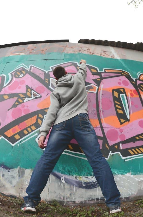 Um indiv?duo novo em um hoodie do cinza pinta grafittis em c cor-de-rosa e verde fotografia de stock