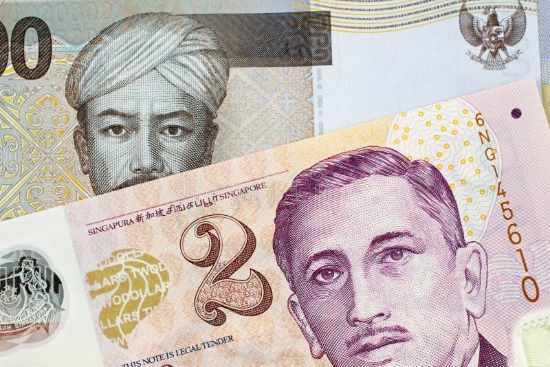 Um indonésio 2000 cédulas da rupia com uma cédula de dois dólares de Cingapura fotos de stock royalty free