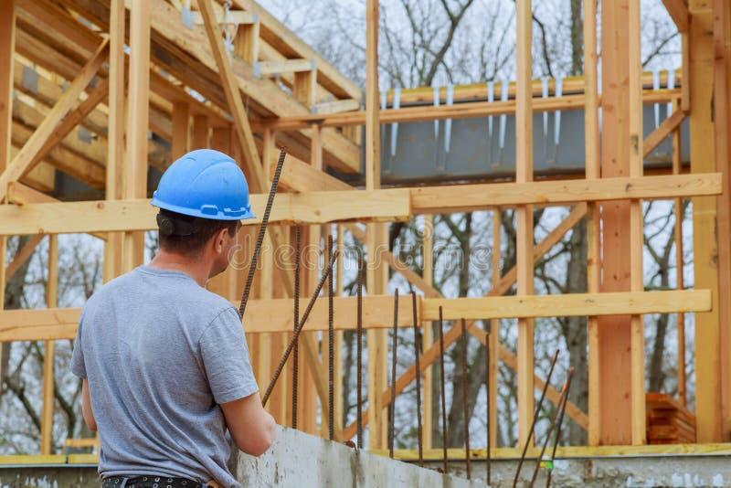 Um inspetor de construção examina uma construção nova da casa no canteiro de obras que verifica a construção nova em andamento imagem de stock