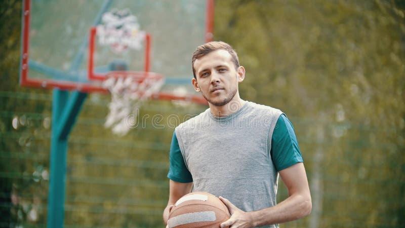 Um instrutor considerável do homem mim que estou em uma terra de esportes e que guardo uma bola do basquetebol imagens de stock royalty free