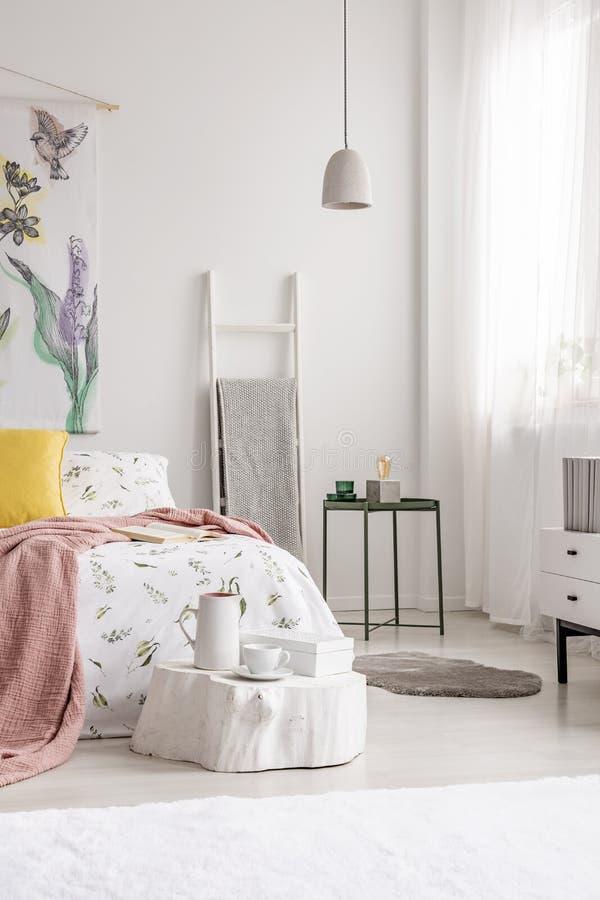 Um interior fresco acolhedor do quarto no branco com uma cama vestiu-se nas folhas, nos descansos e na cobertura Foto real fotografia de stock royalty free