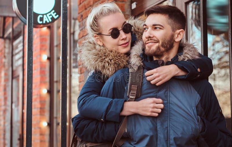Um inverno dos pares atrativos felizes que veste revestimentos está passando o tempo junto fora imagens de stock