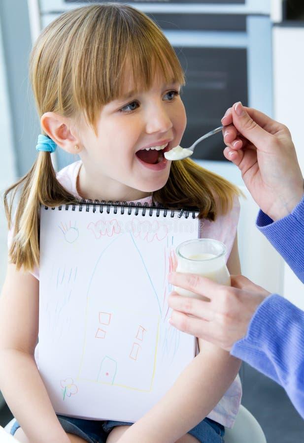 Um iogurte comer da jovem mulher e da menina na cozinha foto de stock royalty free