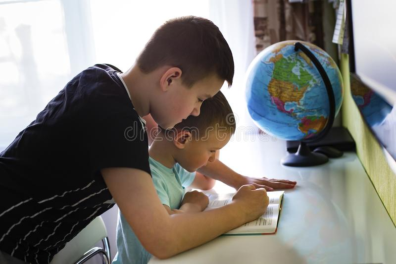 Um irmão mais idoso ensina lições com irmão mais novo imagem de stock