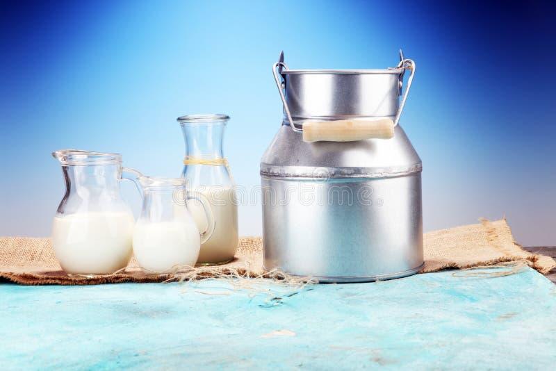 Um jarro de leite e de vidro do leite em uma tabela de madeira fotografia de stock royalty free