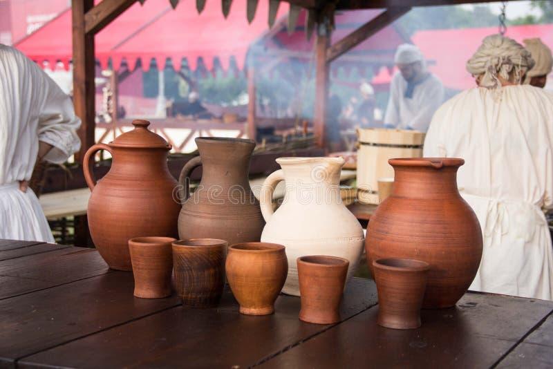 Um jarro do vinho e um grupo de copos da argila na tabela de madeira fotografia de stock