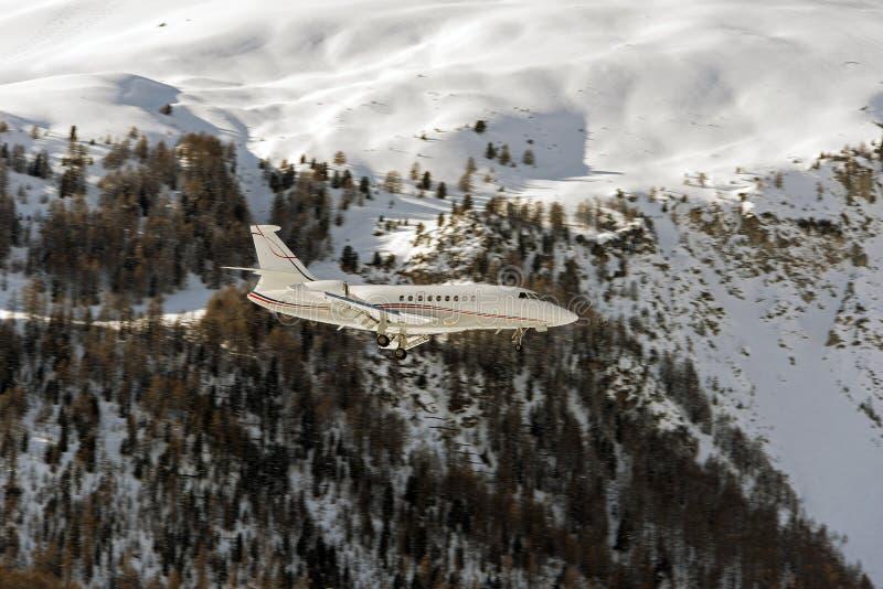 Um jato privado que aterra ao aeroporto de St Moritz em montanhas nevado nos cumes switzerland imagem de stock