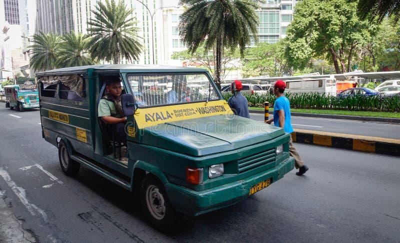 Um jeepney que corre na rua de Ayala em Manila, Filipinas fotografia de stock