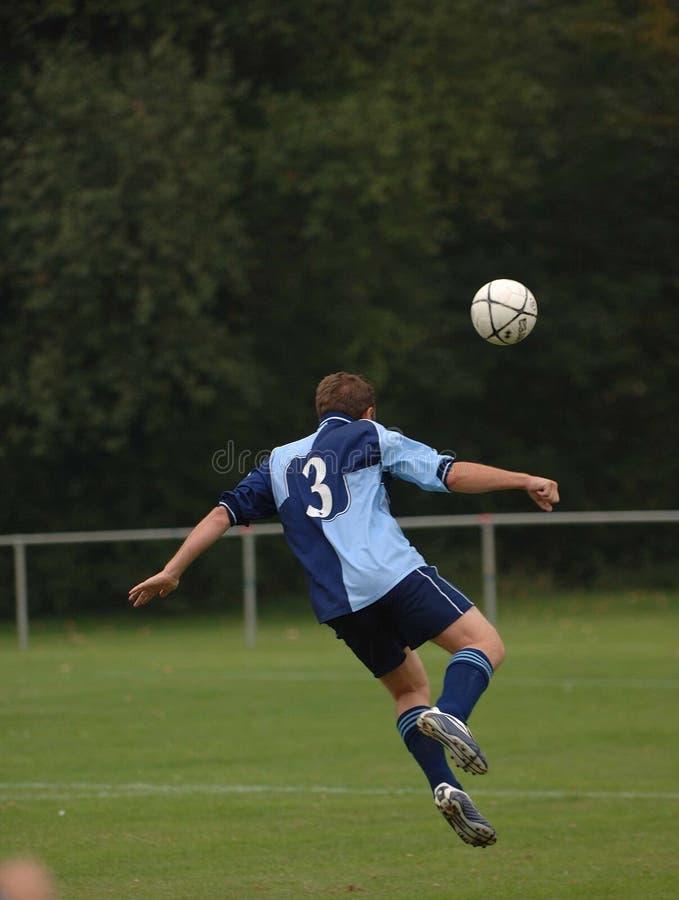 Um jogador de futebol que joga o futebol fotos de stock royalty free