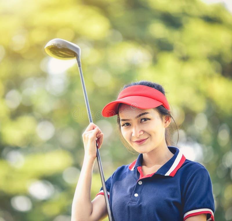 Um jogador de golfe fêmea asiático está sorrindo com uma expressão feliz nela fotos de stock royalty free