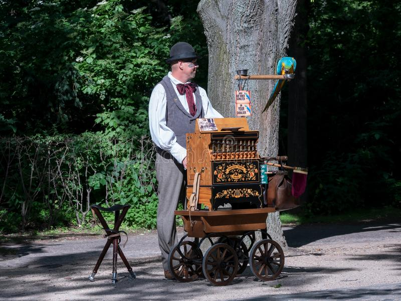 Um jogador do órgão de tambor com um papagaio em Berlim, Alemanha fotografia de stock royalty free