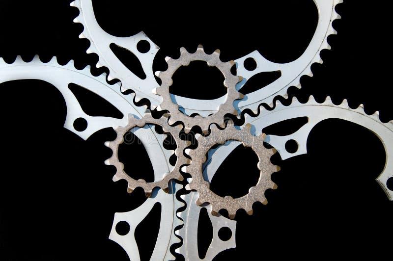 Um jogo do close up dos chainrings da bicicleta no preto fotografia de stock royalty free