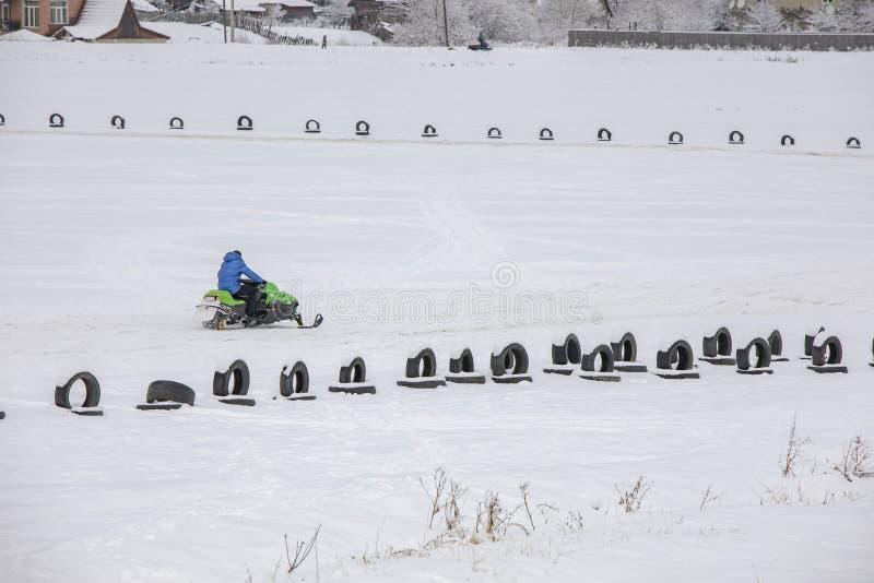 Um jovem andando de moto de neve na estrada foto de stock