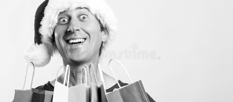 Um jovem animado em Papai Noel segurando sacos de compras Conceito de Natal, venda, desconto e férias Comprador louco de Natal co imagem de stock