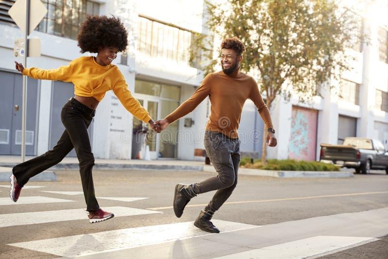 Um jovem casal afro-americano, fascinante, correndo em uma rua da cidade, de mãos dadas, longamente, perto imagem de stock royalty free