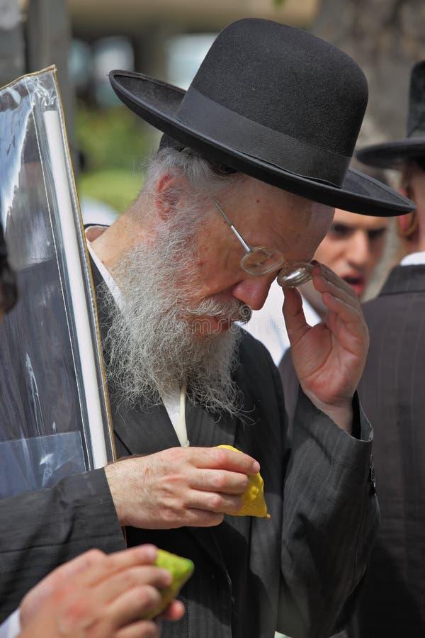 Um judeu ortodoxo idoso no chapéu negro escolhe o citrino