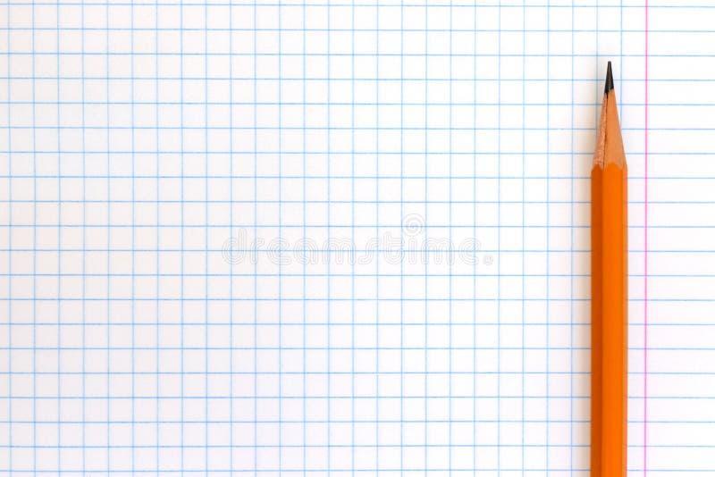 Um lápis amarelo de madeira no papel quadriculado do livro de exercício com espaço da cópia imagem de stock
