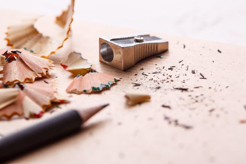 Um lápis cinzento afiado com um apontador do metal na tabela imagem de stock