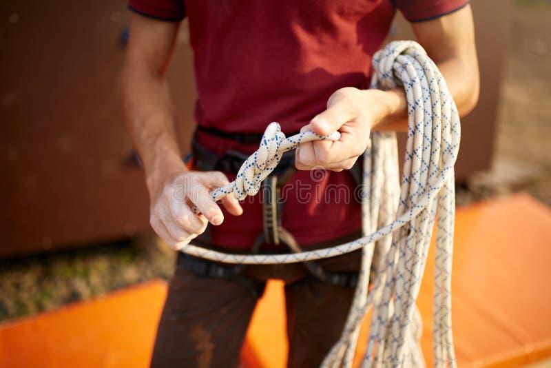 Um laço do montanhista de rocha um o nó em uma corda Uma pessoa está preparando-se para a subida O homem aprende amarrar uma pare imagem de stock royalty free