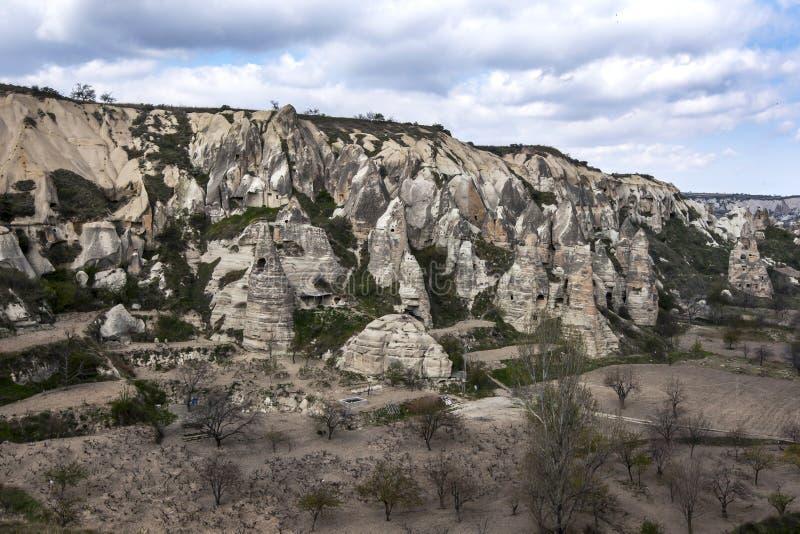 Um lado do monte coberto com as chaminés feericamente perto do museu do ar livre em Goreme na região de Cappadocia de Turquia foto de stock