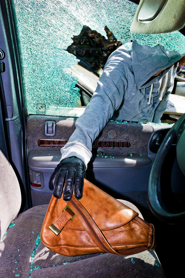 Um ladrão roubou uma bolsa do carro imagem de stock