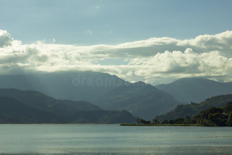 Um lago em um fundo do vale verde da montanha e do céu azul com nuvens brancas imagens de stock royalty free