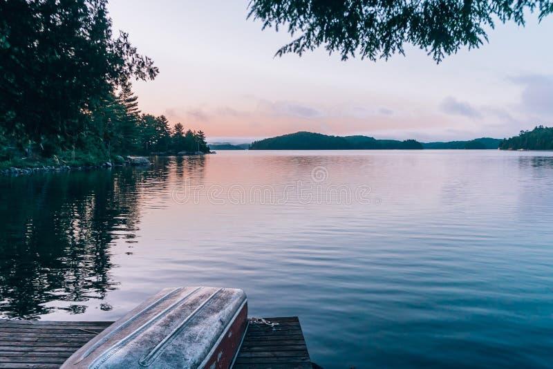Um lago imóvel durante o por do sol com um barco em uma doca foto de stock
