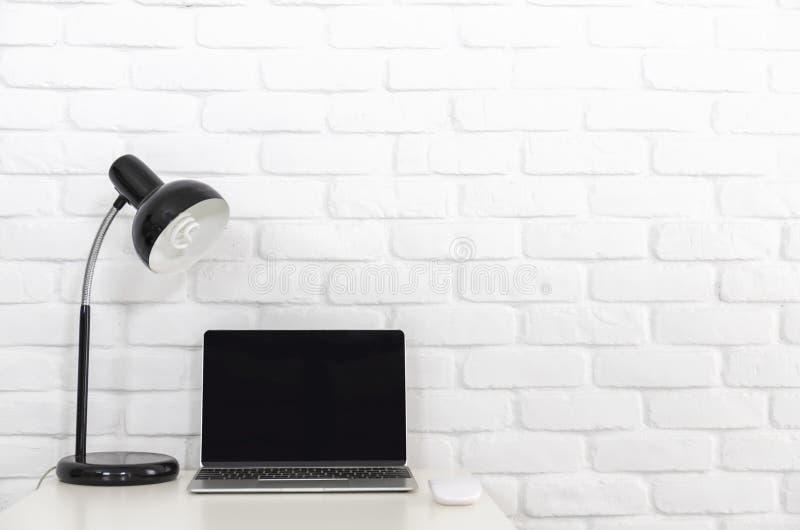 Um laptop da tela vazia na mesa branca com lâmpada e na parede de tijolo branca foto de stock royalty free