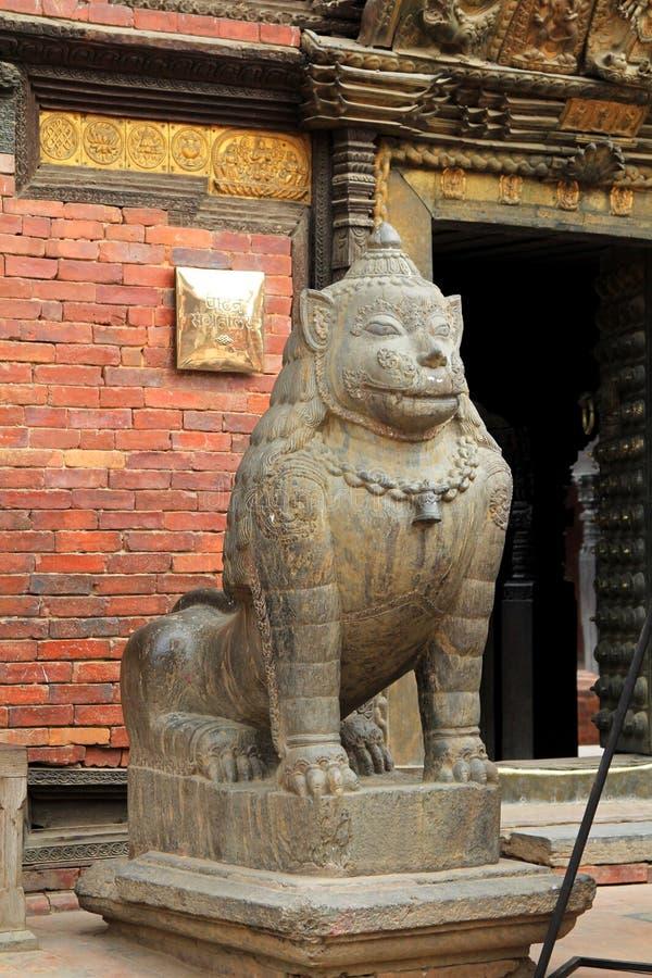 Um leão de pedra enorme que guarda o museu de Patan em Patan, Nepal fotografia de stock