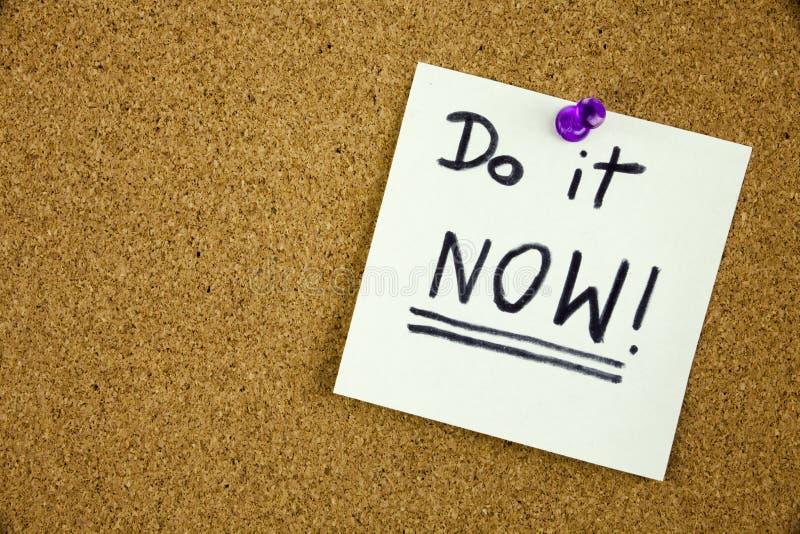 Um lembrete para fazê-lo agora a mensagem, quadro de mensagens com uma nota pegajosa azul com texto fá-lo agora foto de stock